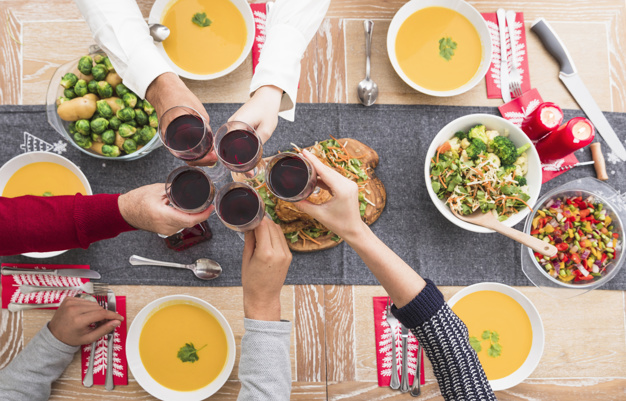 people-clanging-glasses-above-festive-table_23-2147973653
